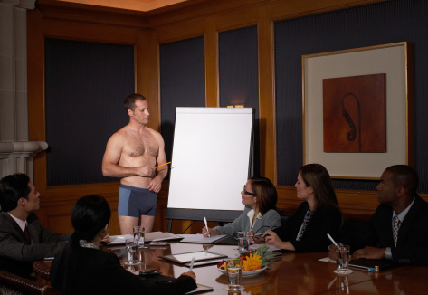 Picture of a woefully underdressed gentleman pointing to a blank flipchart in board room full of suits